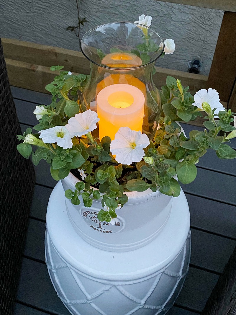 DIY outdoor planter candle holder glowing at night.