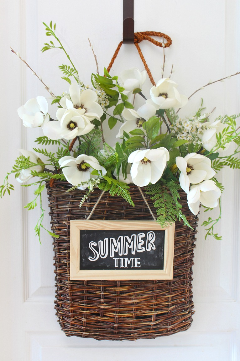 Summer basket wreath with white flowers, greenery, and chalkboard sign.