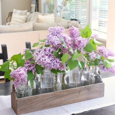 Lilacs used in a pretty centerpiece on a kitchen table.