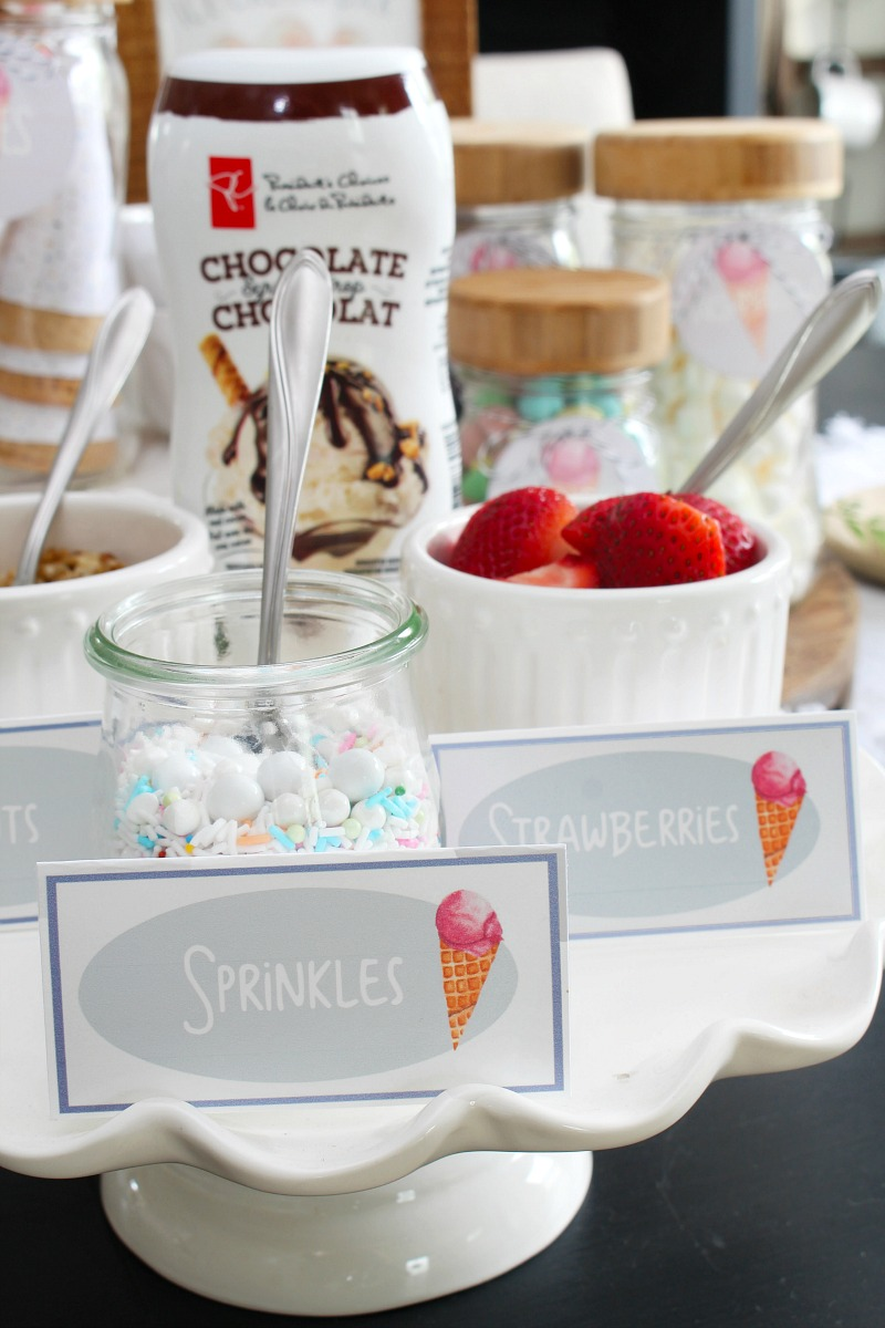 Ice cream sundae bar with toppings on a cake stand.