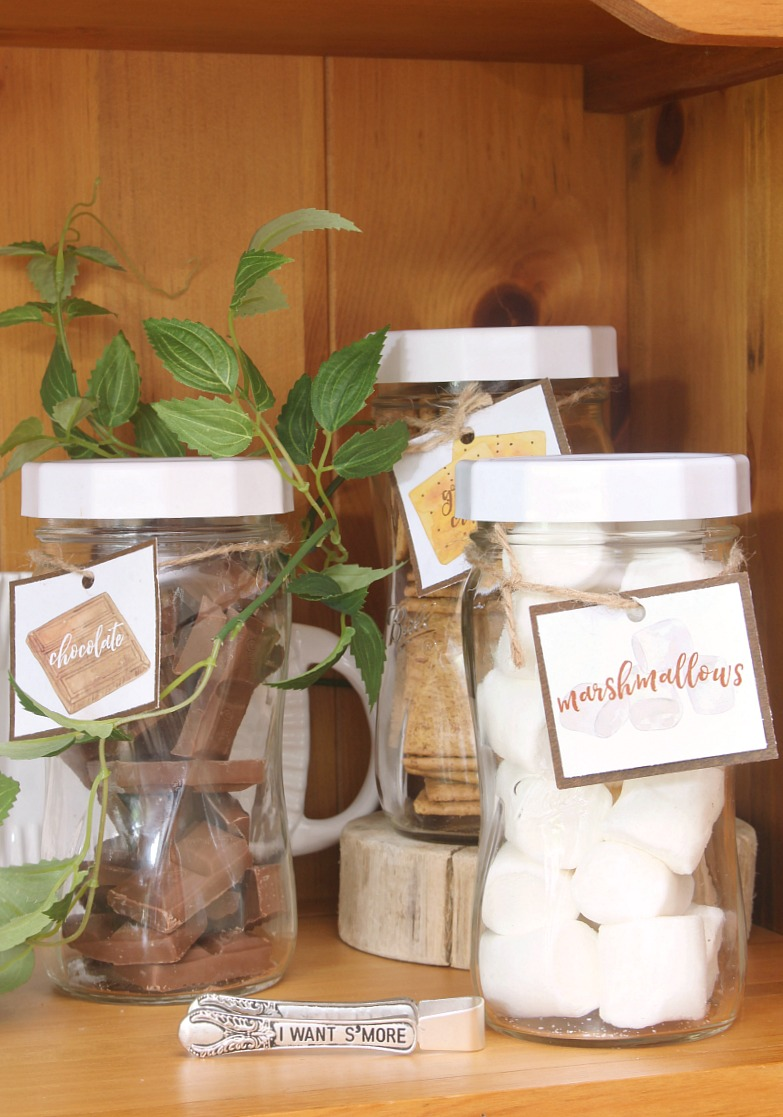 Mason jars filled with ingredients for s'mores with free printable s'mores labels.