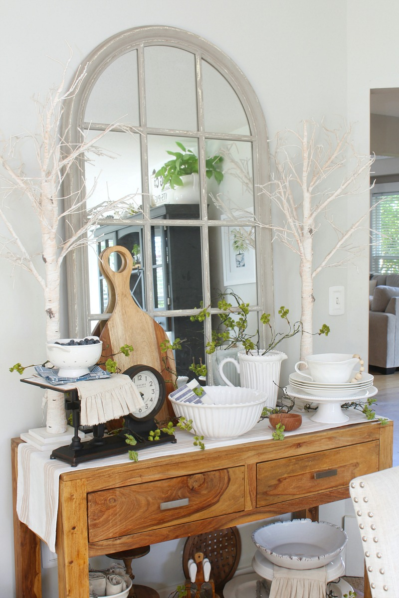 Wood dining room sideboard decorated with blues, whites, and pops of greenery.
