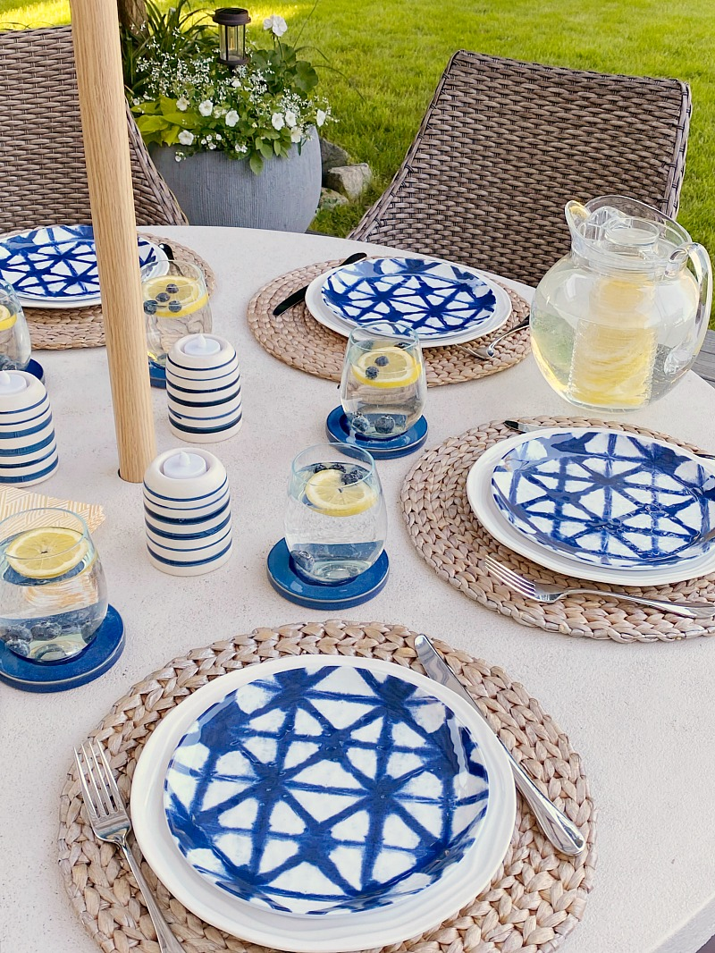 Pretty summer tablescape on an outdoor patio with blue and yellow accents.