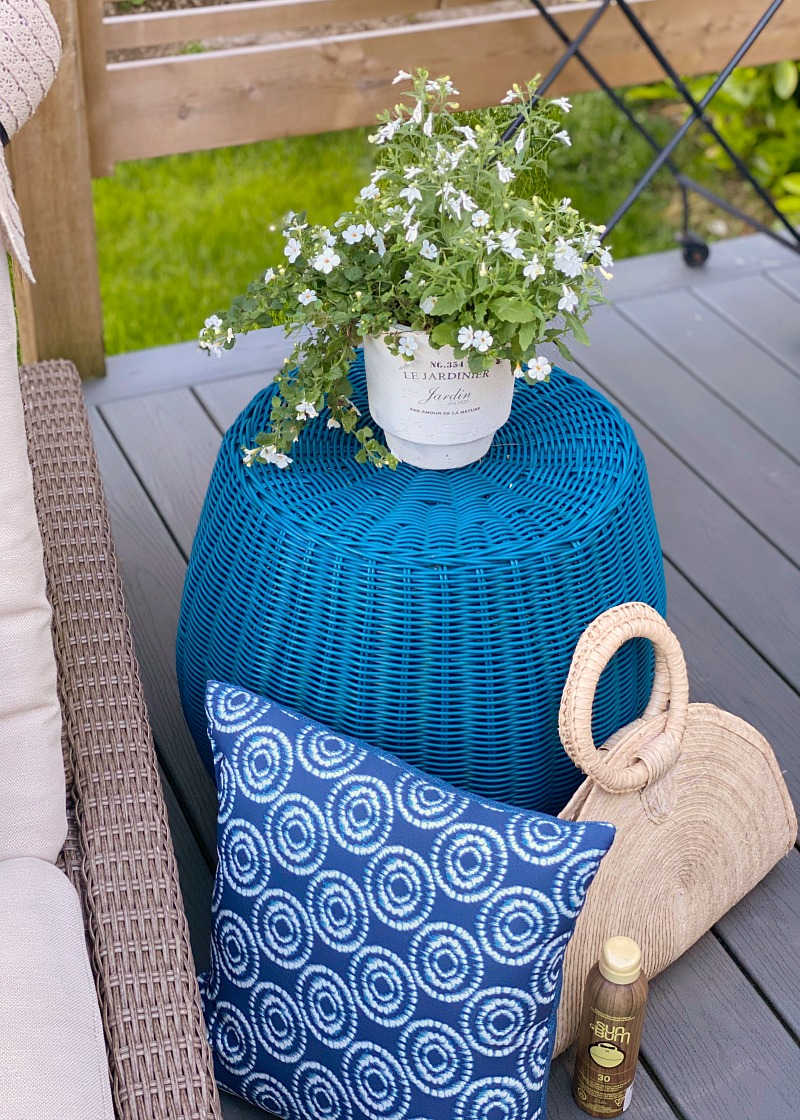 Outdoor blue wicker side table on an outdoor patio.