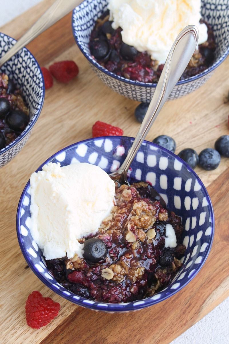 Berry crisp with ice cream in blue bowls.