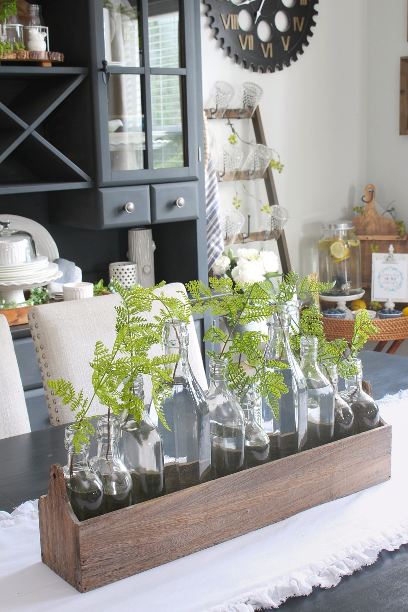 Summer centerpiece with various glass jars with ferns in a wood tray.