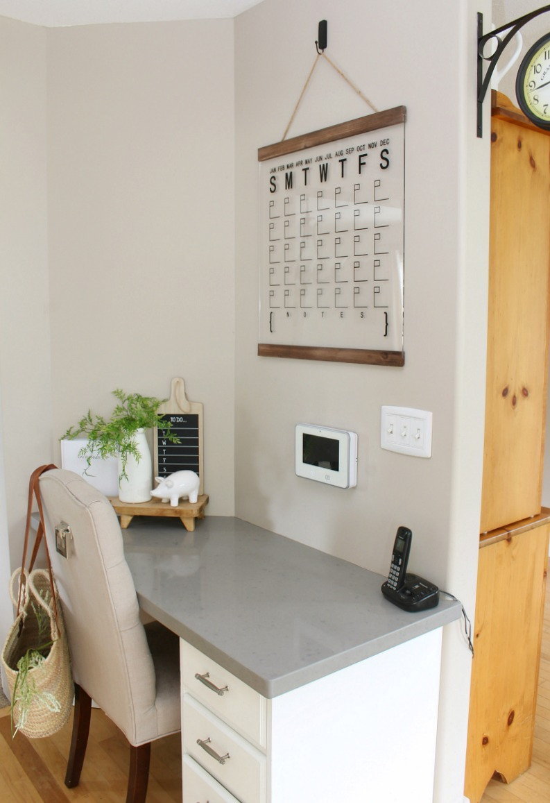 Small desk space off the kitchen with an acrylic calendar.