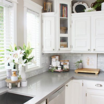 White kitchen with grey quartz countertops decorated for summer.