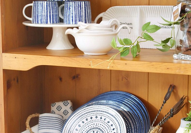 Summer hutch decorated with outdoor dinnerware and everything needed for a summer night of s'mores and hot chocolate.