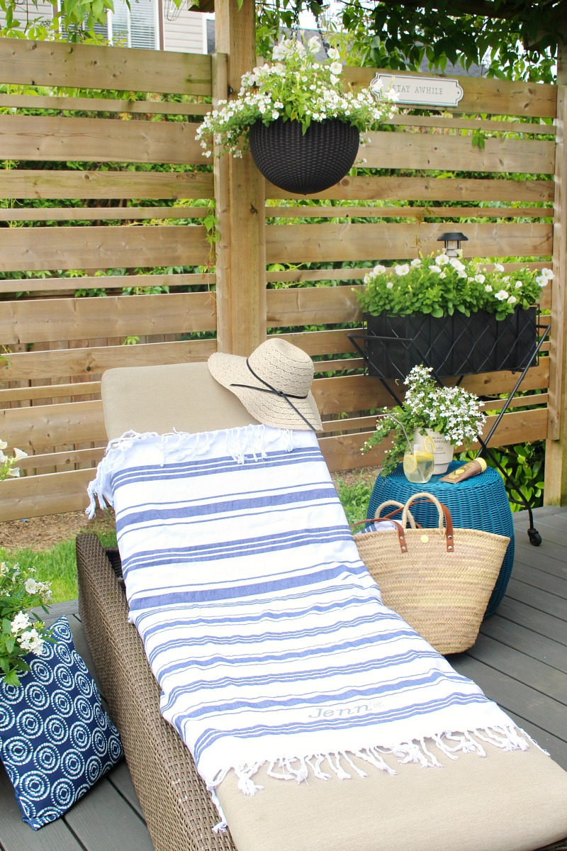 Blue and white striped DIY custom beach towel on a patio lounger.