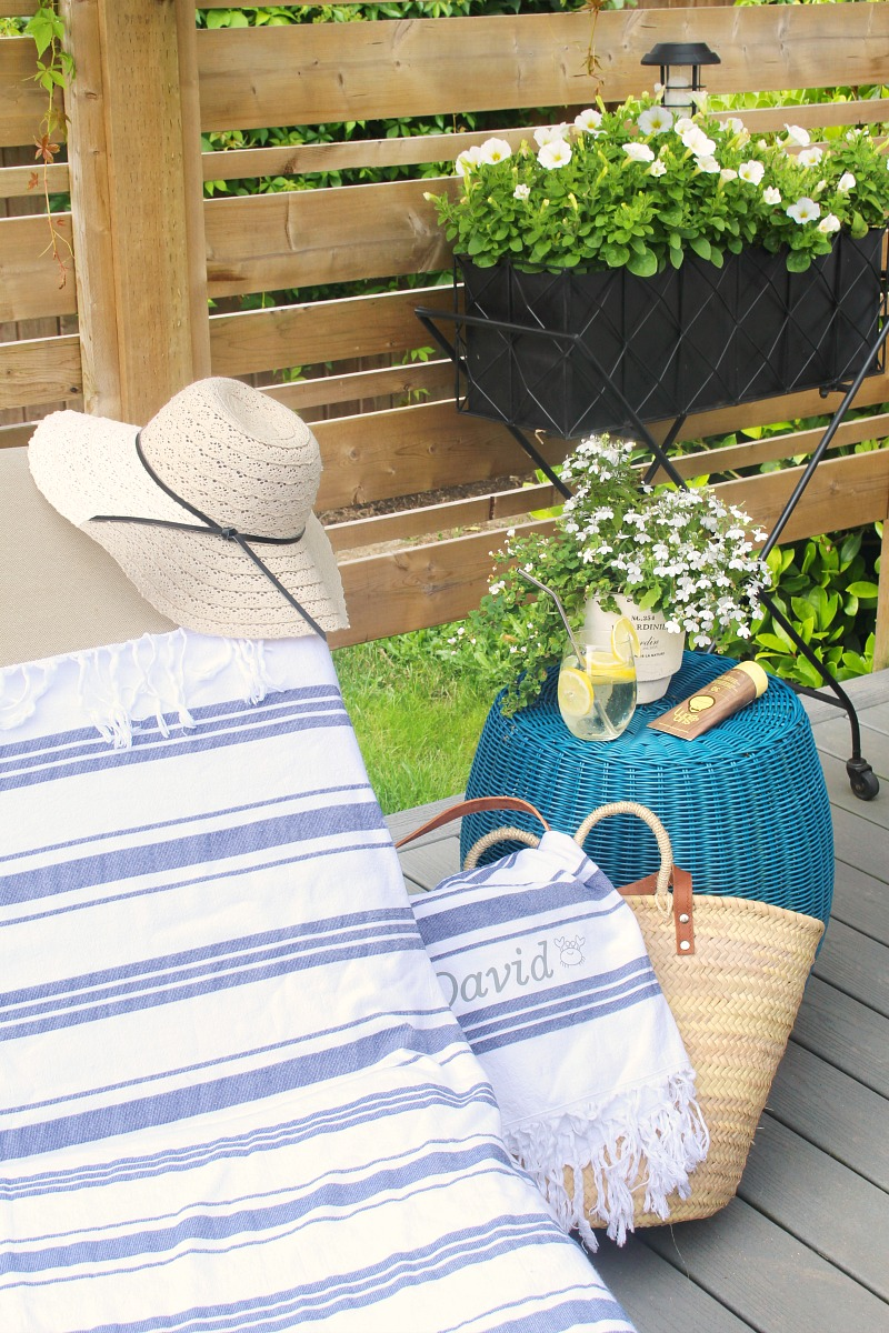 Summer patio with custom beach towels on a lounger and beach tote.