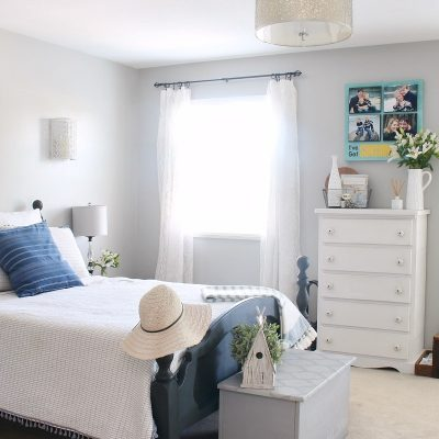 Bedroom decorated for summer with blue and white bedding.