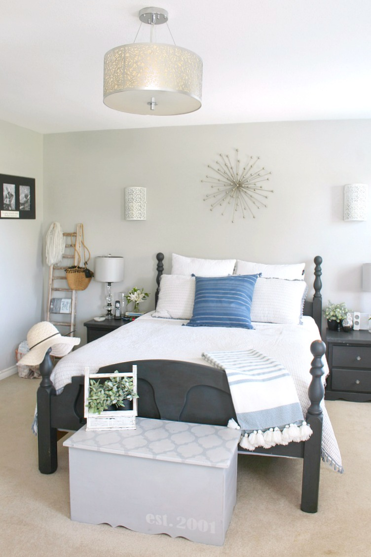 Bedroom decorated for summer with black painted furniture and white and blue bedding.