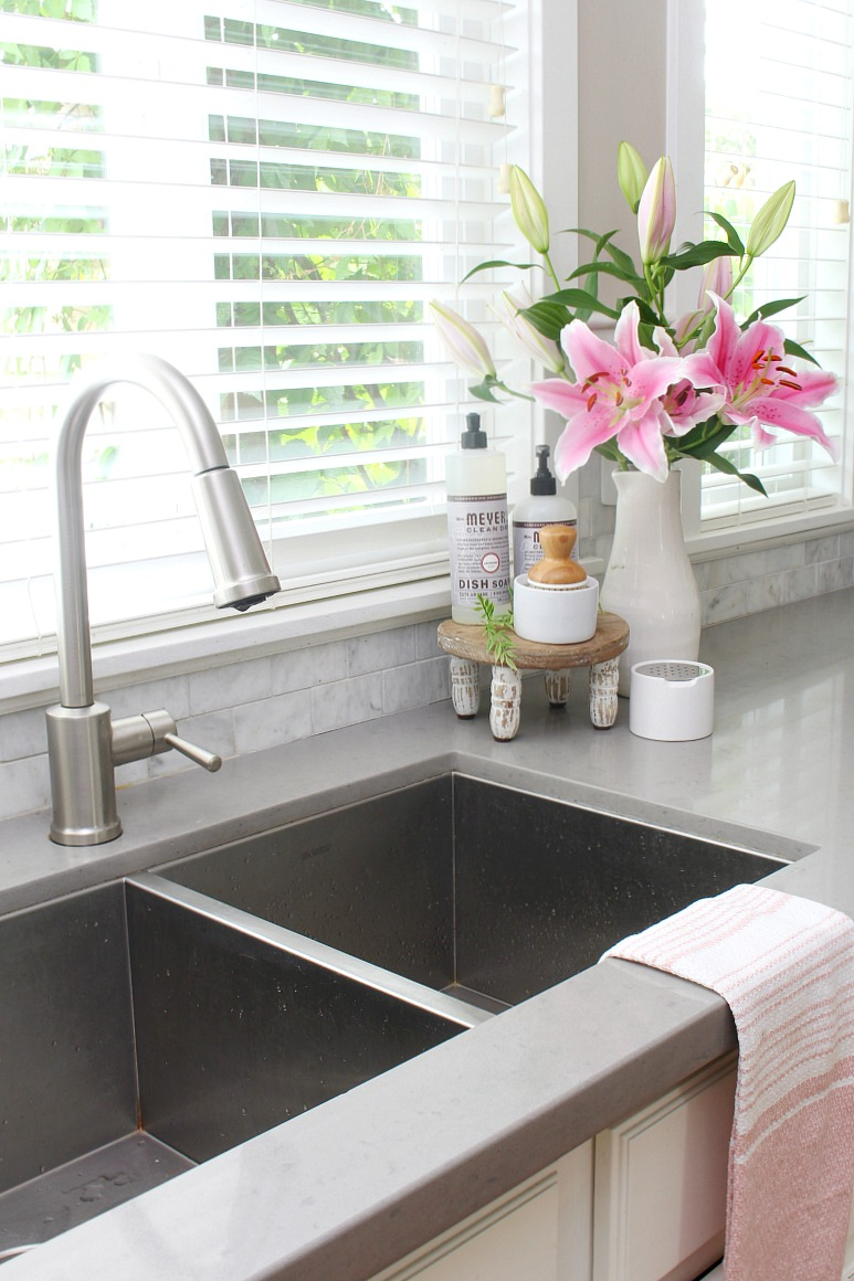 Pretty fruit fly trap with DIY recipe sitting beside a kitchen sink with vase of lillies.