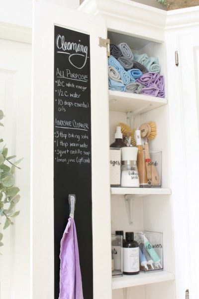 Organized cleaning closet with cleaning cloths and cleaning supplies.
