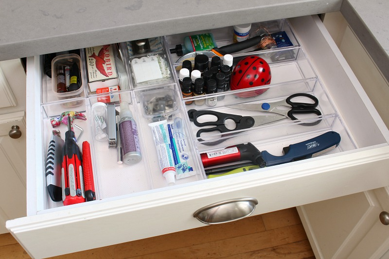 Kitchen junk drawer organized with acrylic bins.