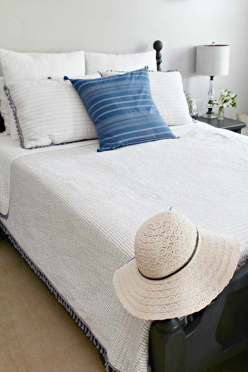 White summer bedding with pops of blue.