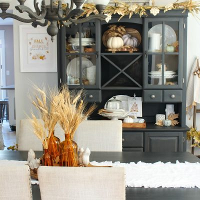 Beautiful farmhouse style dining room decorated for fall with neutral fall colors.