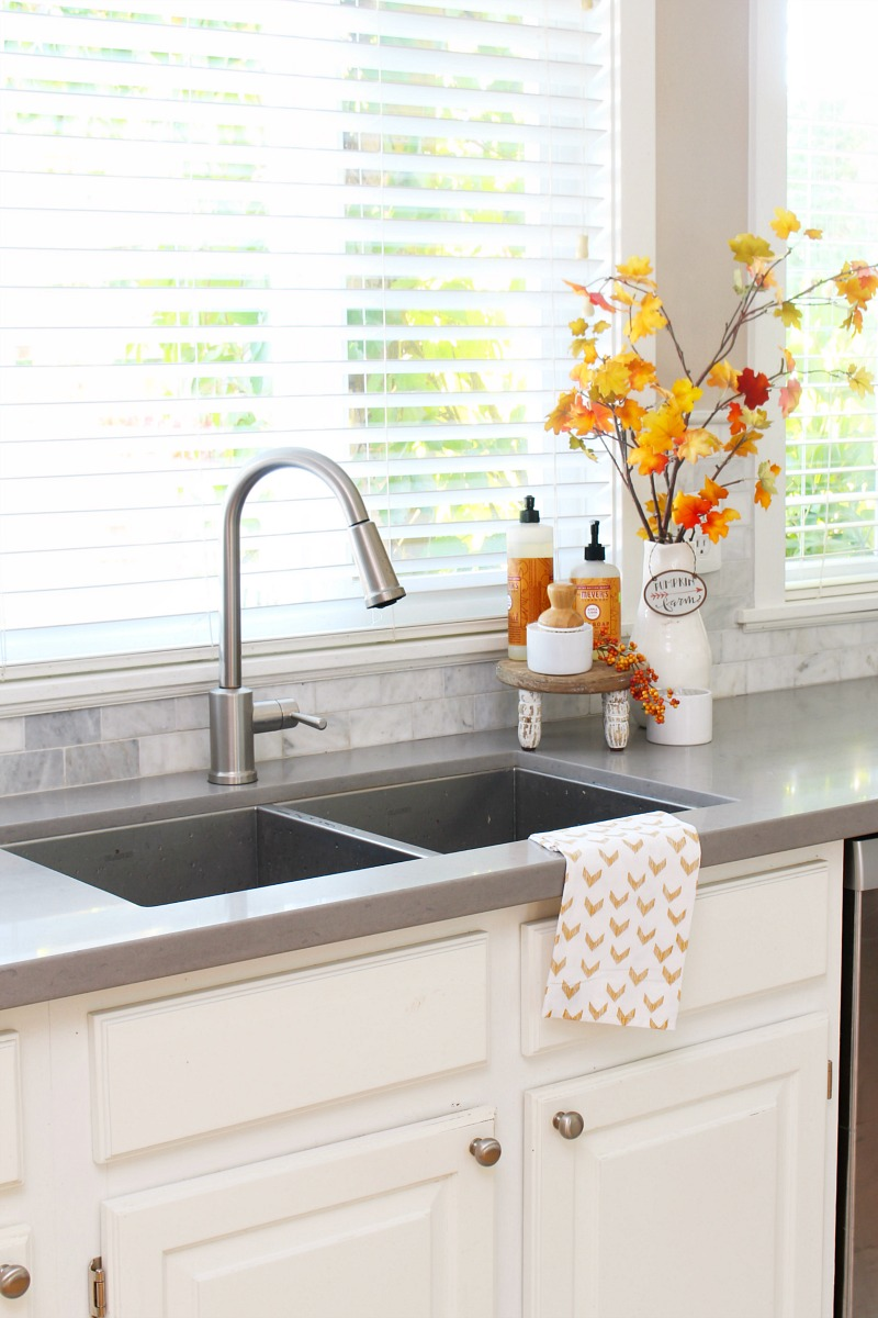 Kitchen sink dressed up for fall with seasonal soaps and a fresh kitchen towel.