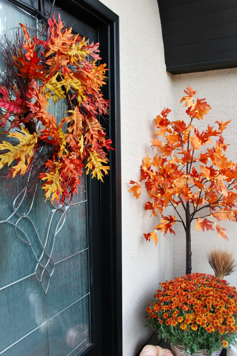 Colorful fall front porch with faux lighted maple trees.
