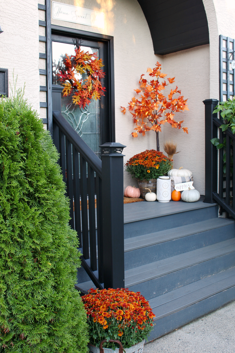 Colorful front porch with lighted maple trees and orange mums.