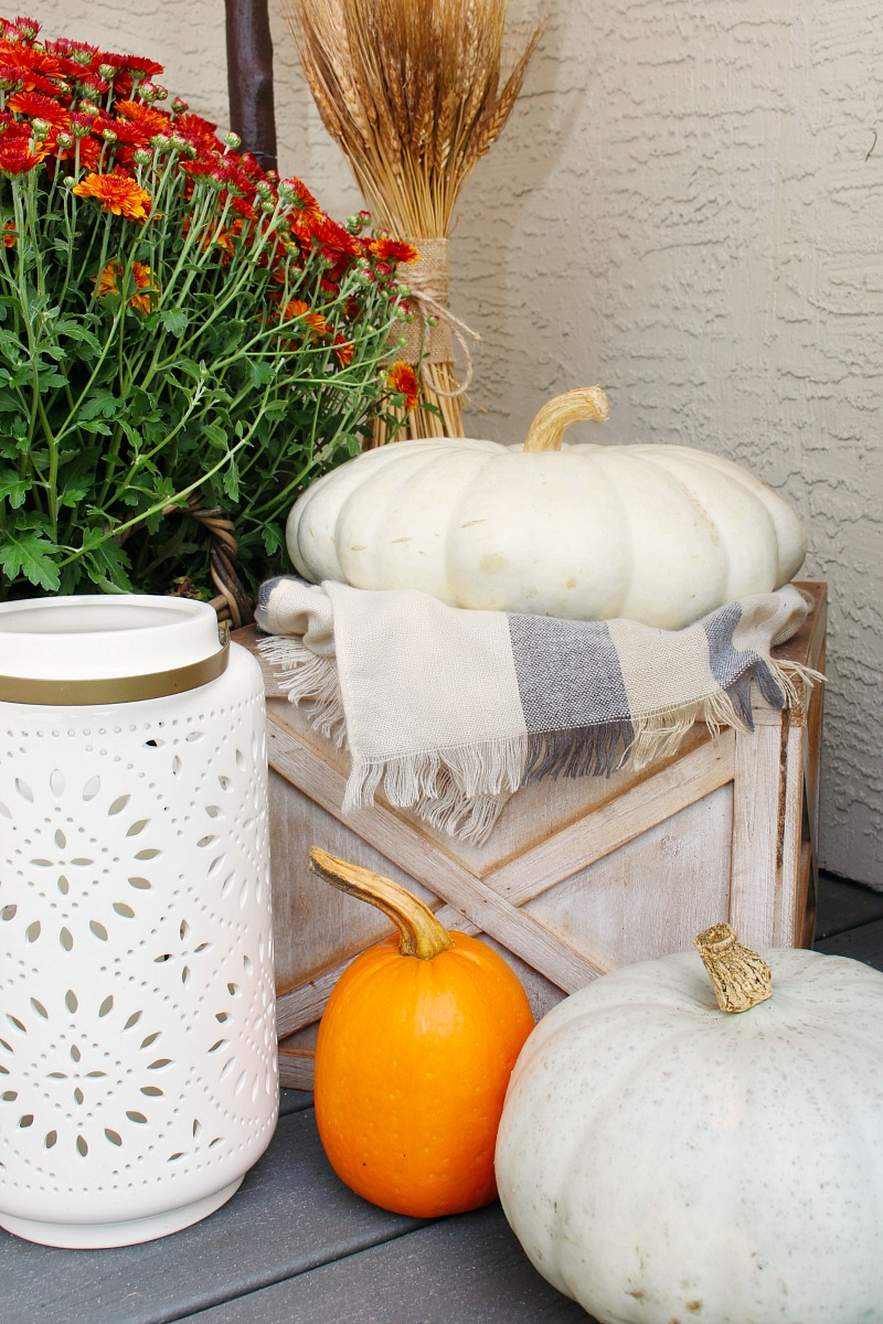 Fall front porch decor with pumpkins and mums.