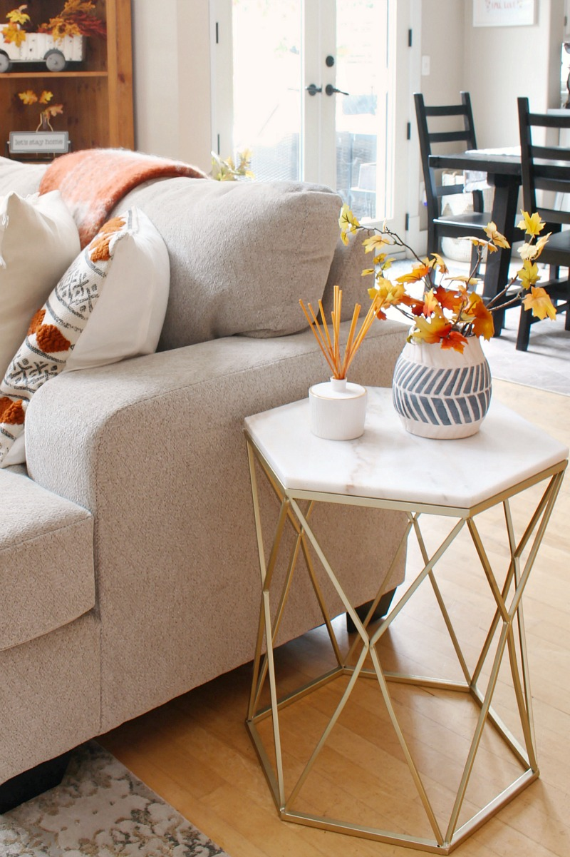 Gold and marble side table decorated with a fall reed diffuser and faux fall stems.