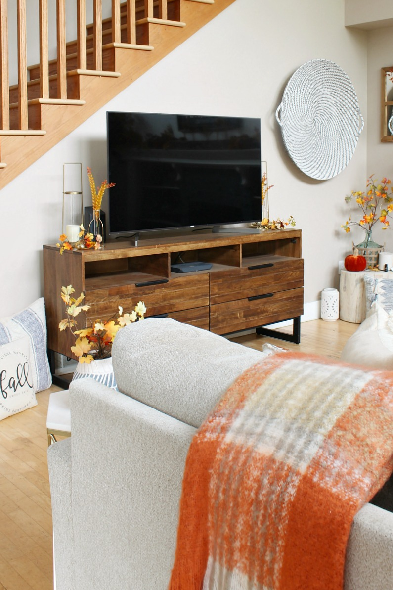 Cozy fall living room decor with wood television console.
