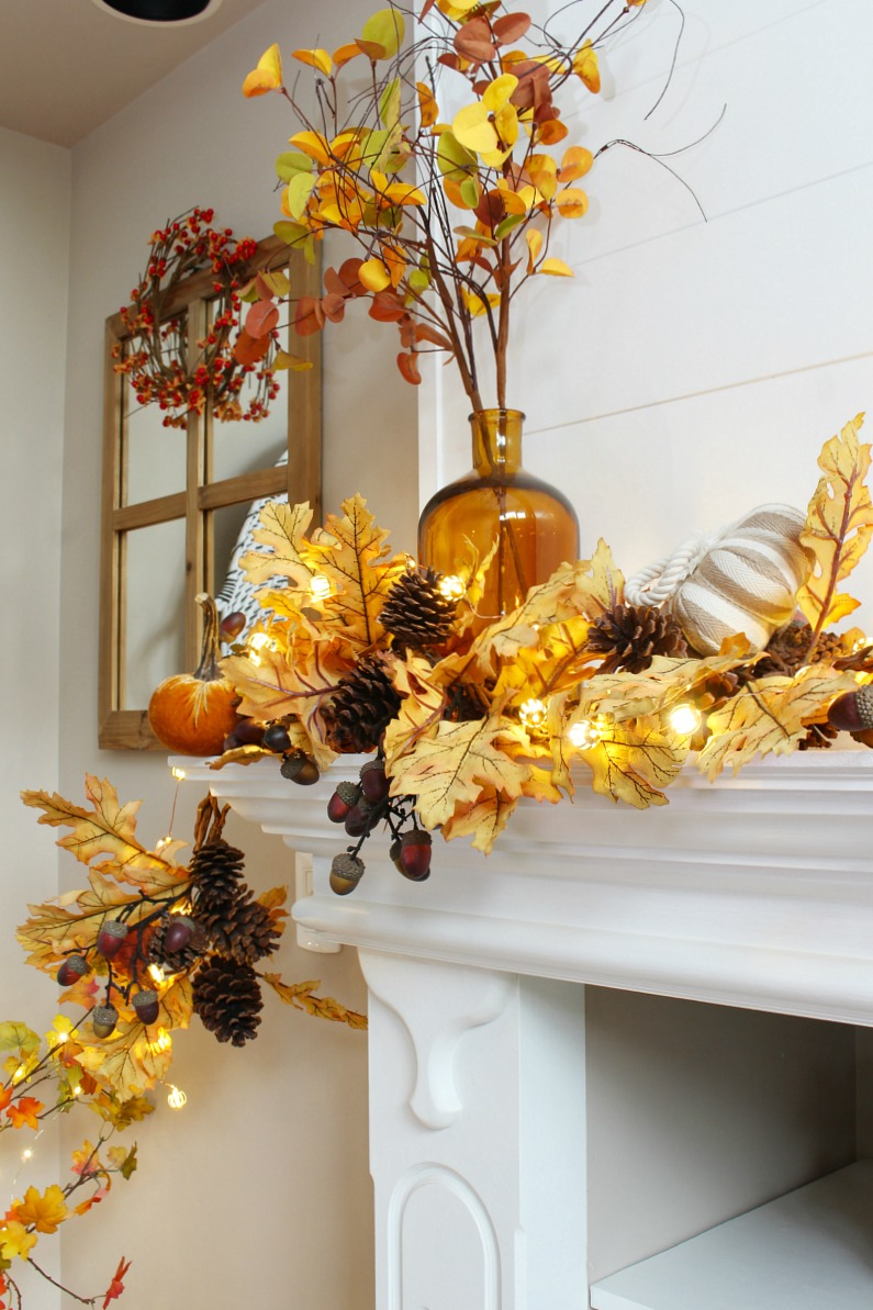 Amber glass vase used on a fall mantel with a golden oak garland and fall lights.