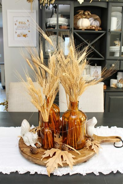 Pretty fall centerpiece with ceramic squirrels and amber glass bottles.