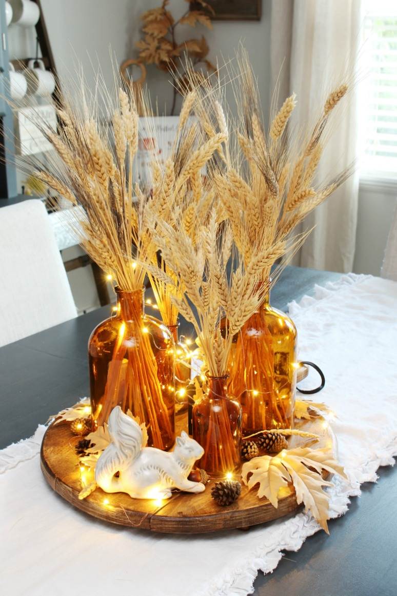 Pretty fall centerpiece with amber glass bottles and wheat.