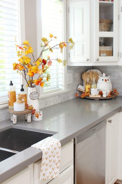 Beautiful farmhouse style white kitchen decorated for fall wth traditional fall colors.
