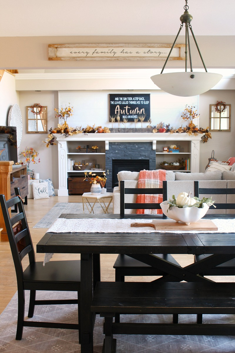Farmhouse style kitchen table decorated for fall in an open living design.