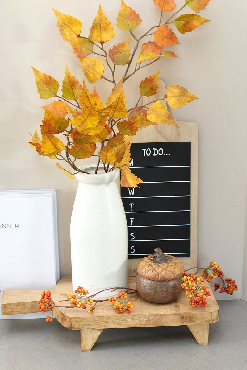 Cute fall vignette with faux stems and a fall candle.