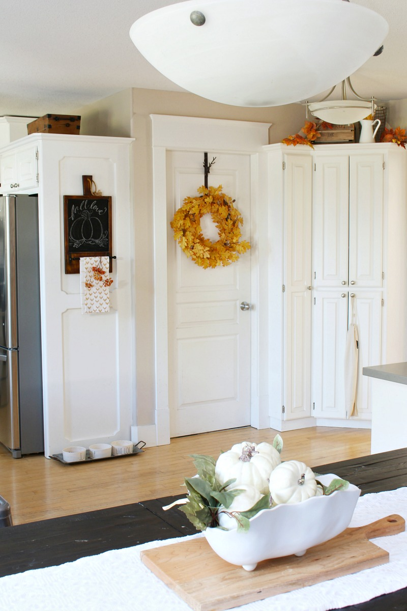 White fall kitchen with bowl of pumpkins on the kitchen table.