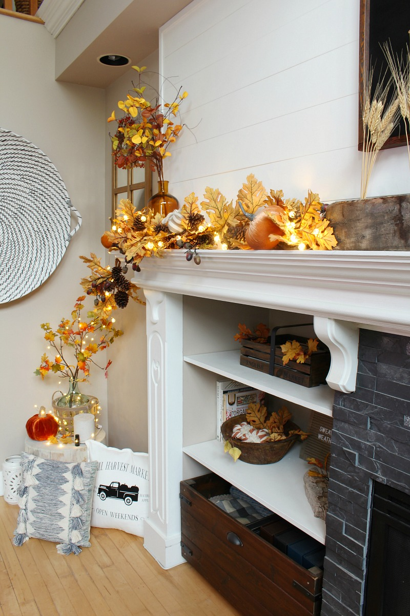 Fall mantel decorated with oak garland, amber glass and lights.