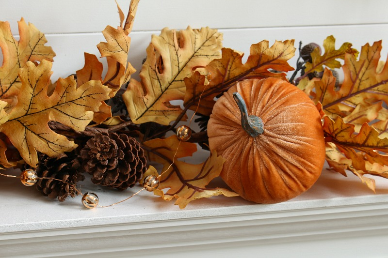 Fall mantel garland with oak leaves, pumpkins, and fall lights.