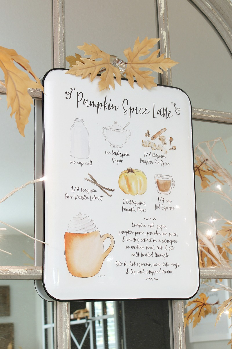 Pumpkin spice latte sign hanging on a mirror.