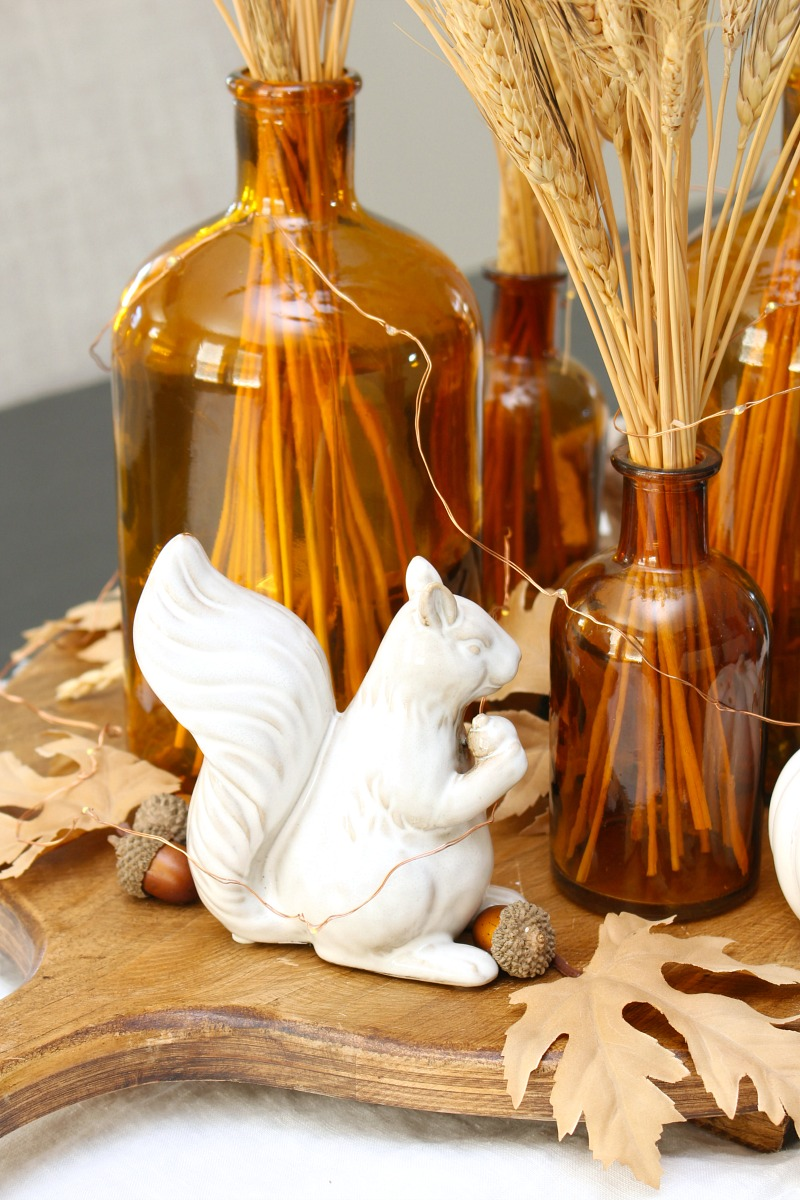 Cute fall centerpiece with glass amber bottles and ceramic squirrels.