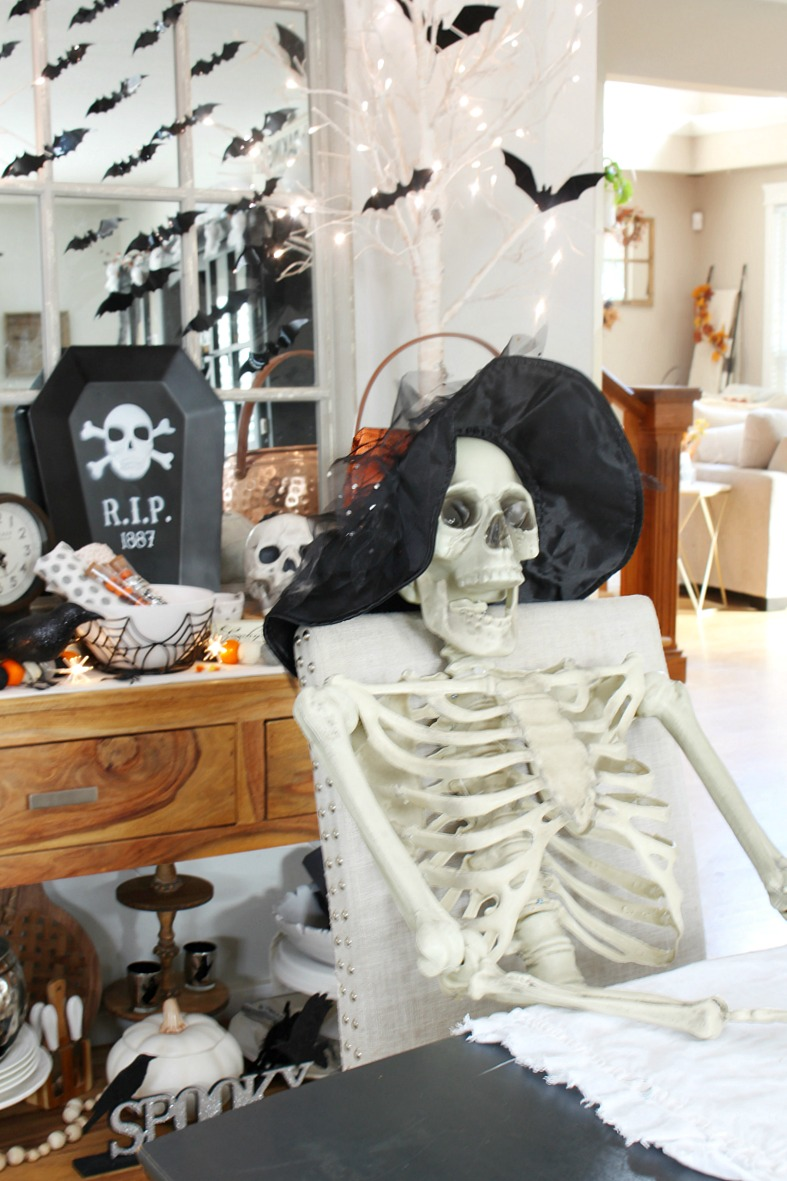 Skeleton sitting at a dining room table decorated for Halloween.