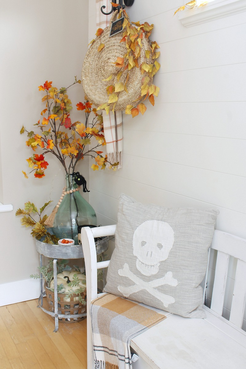 Front entry way with bench and Halloween pillow.