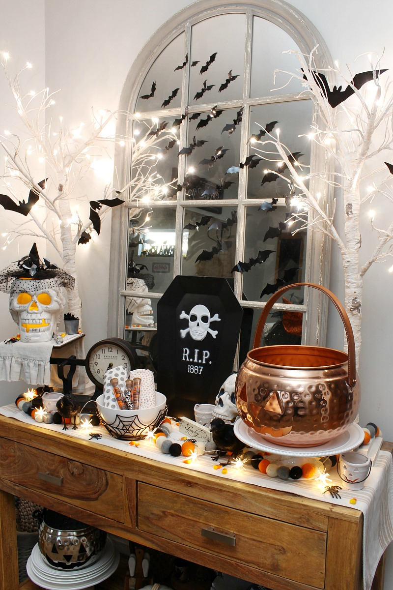 Dining room sideboard decorated for Halloween with lights.
