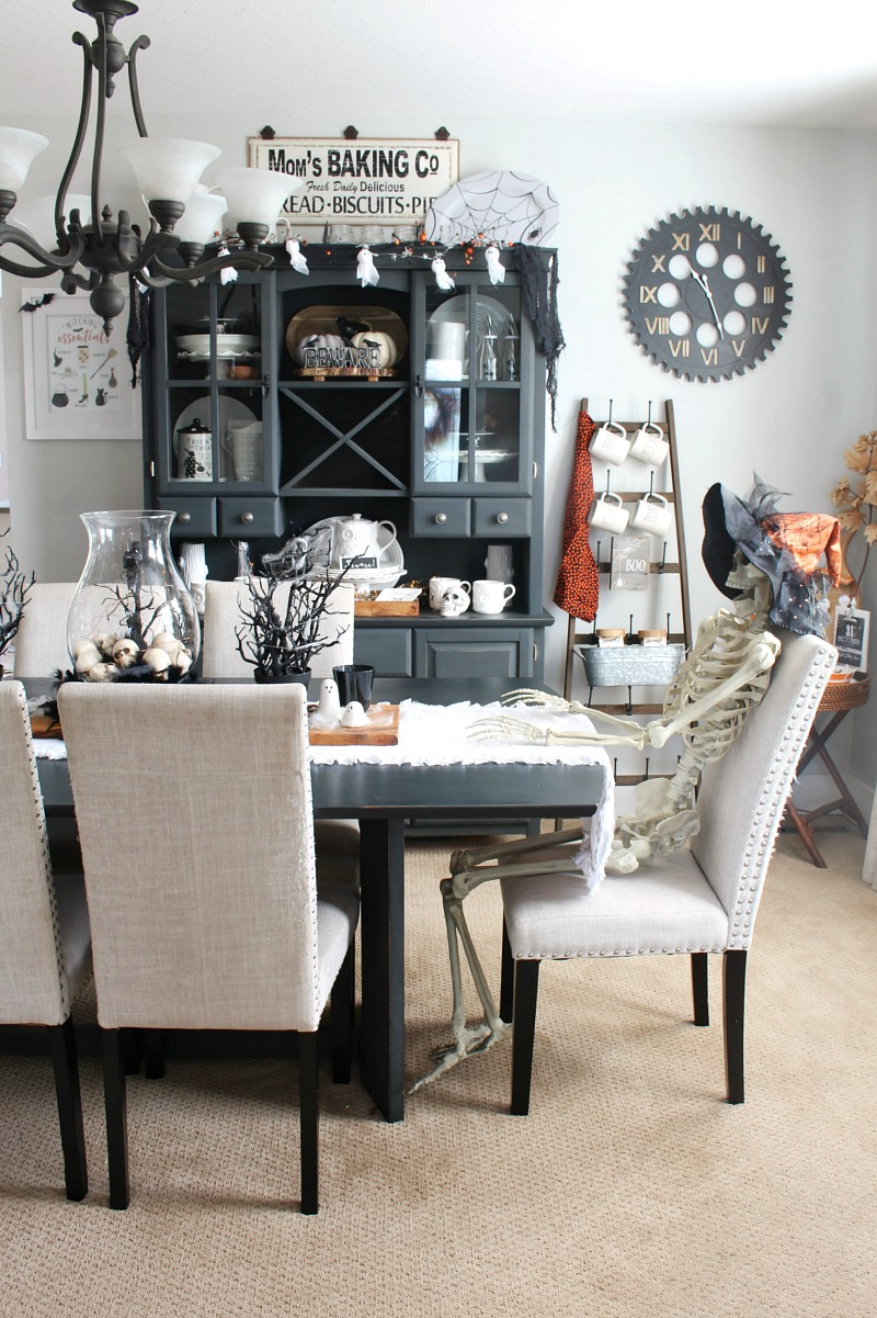 Dining room space decorated for Halloween with skeleton.