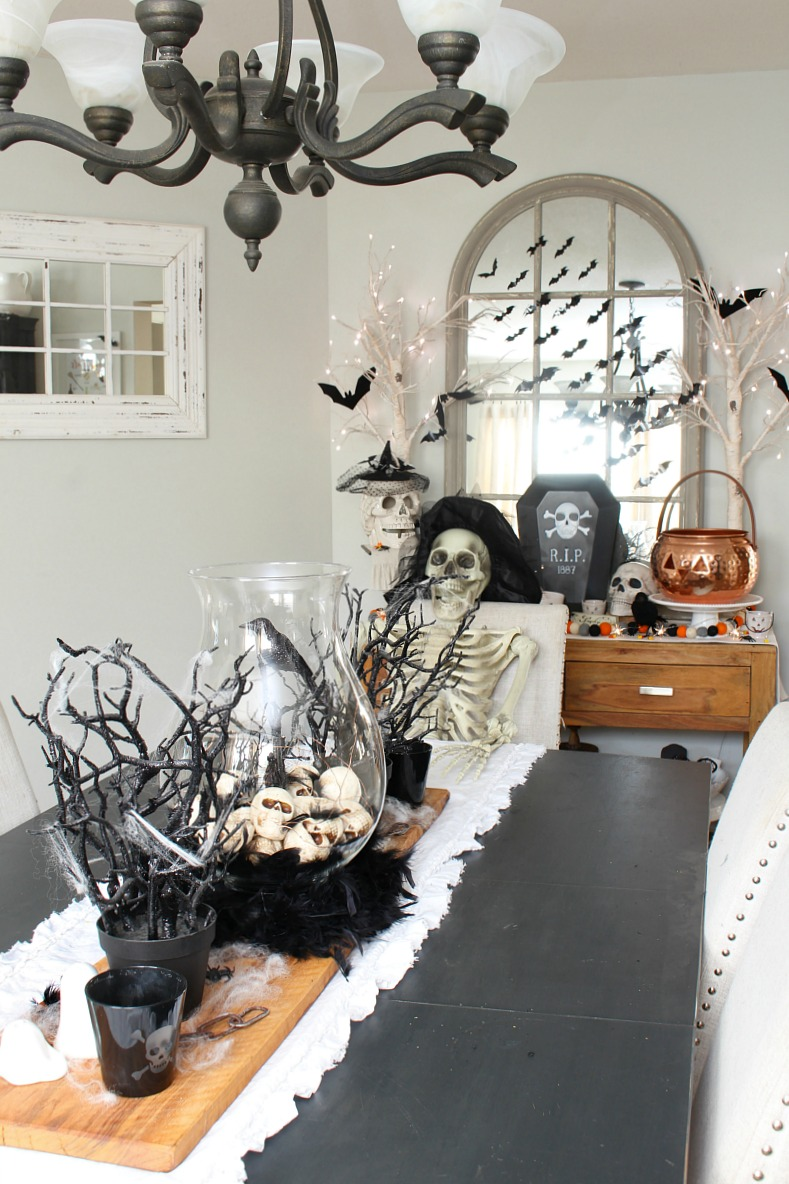 Halloween dining room decorated with skulls, bats, and skeletons.
