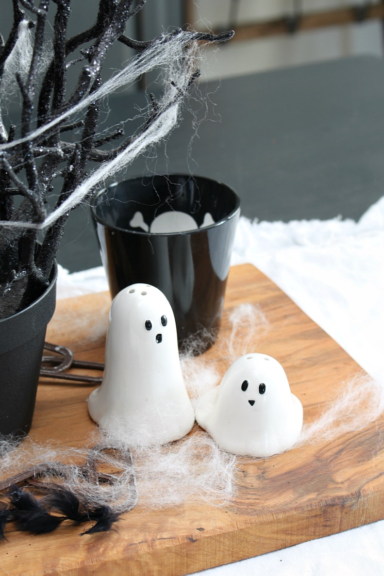 Ghost salt and pepper shakers in a dining room decorated for Halloween.