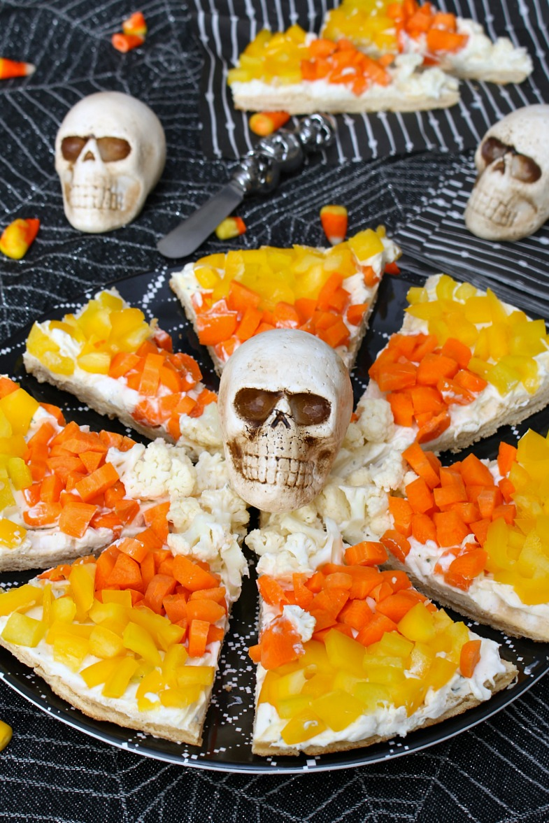 Candy corn Halloween veggie pizza on a Halloween tablecloth.