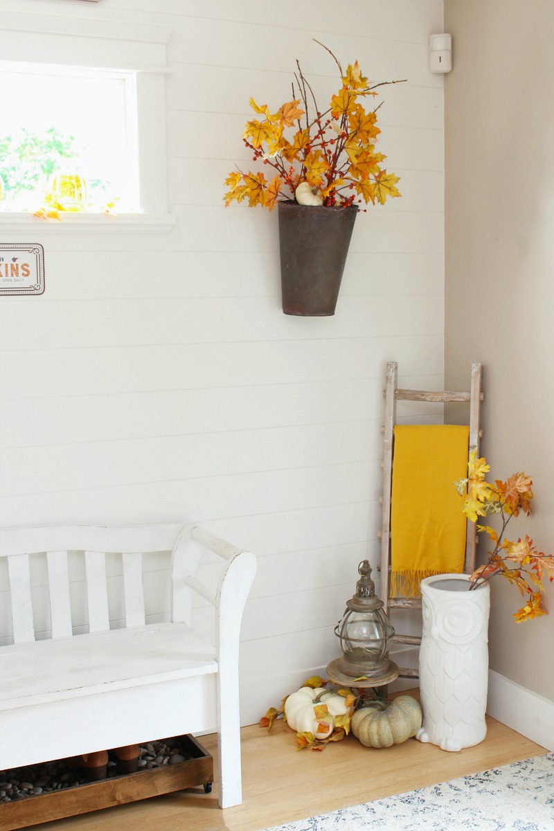 Front entryway decorated for fall with orange and yellow fall colors.