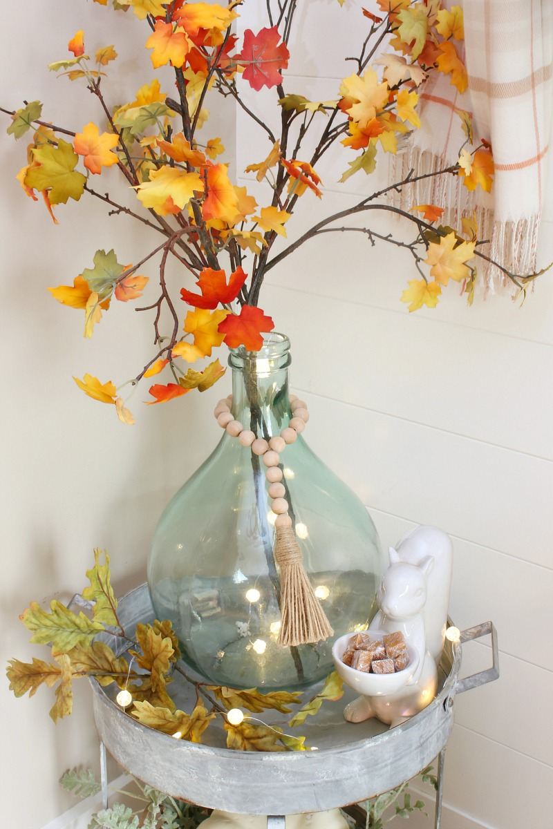 Side table in foyer decorated for fall.