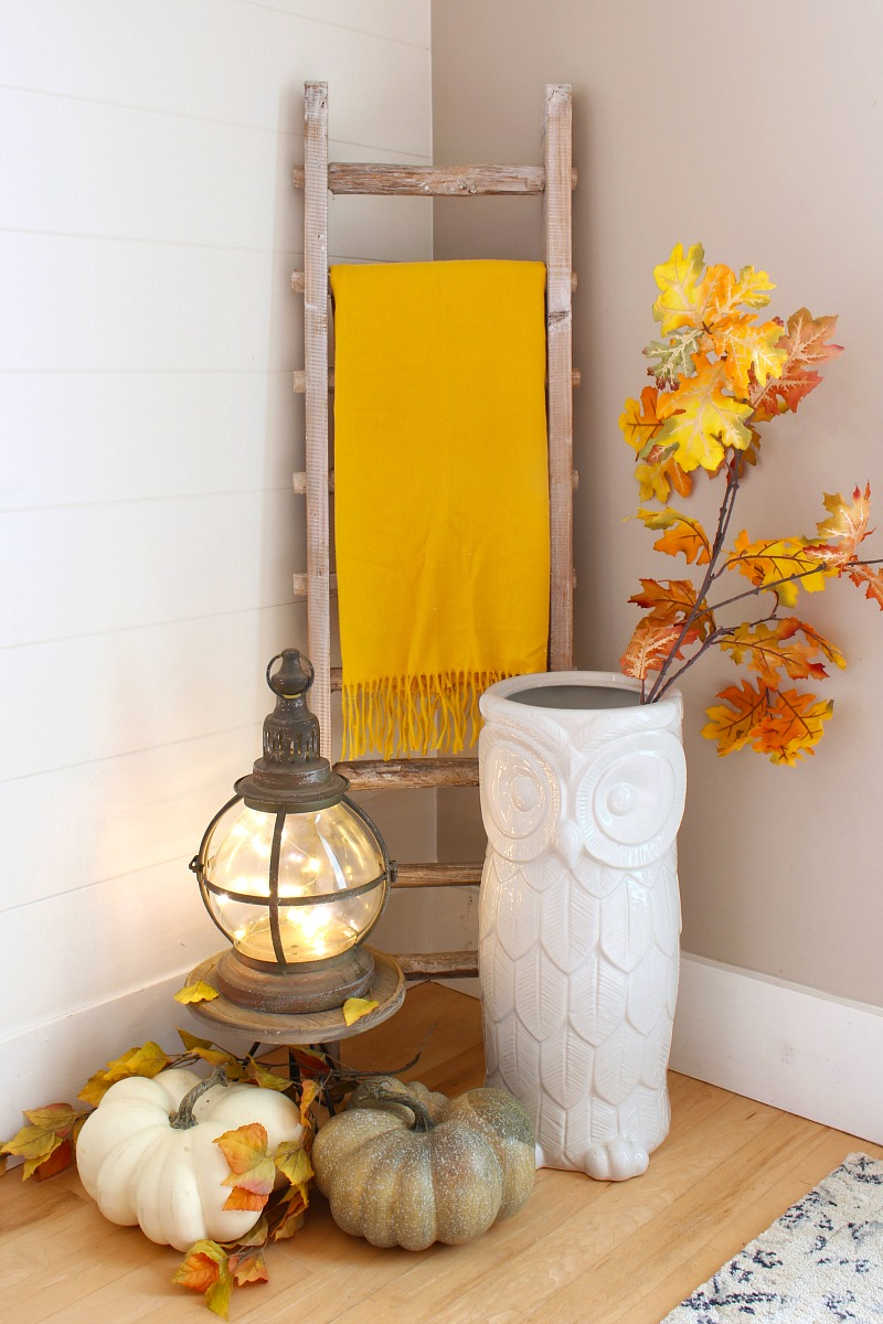 Fall foyer decorated with pumpkins and yellow and orange faux stems.