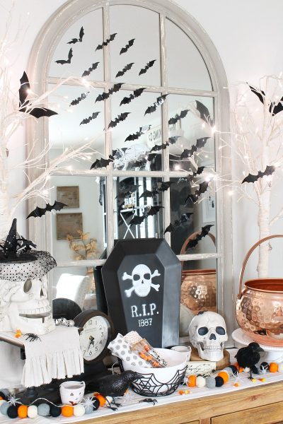 Dining room sideboard decorated for Halloween with bats and skeletons.